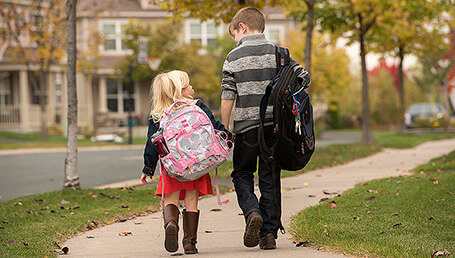 Child with cystinosis walking to school with sibling